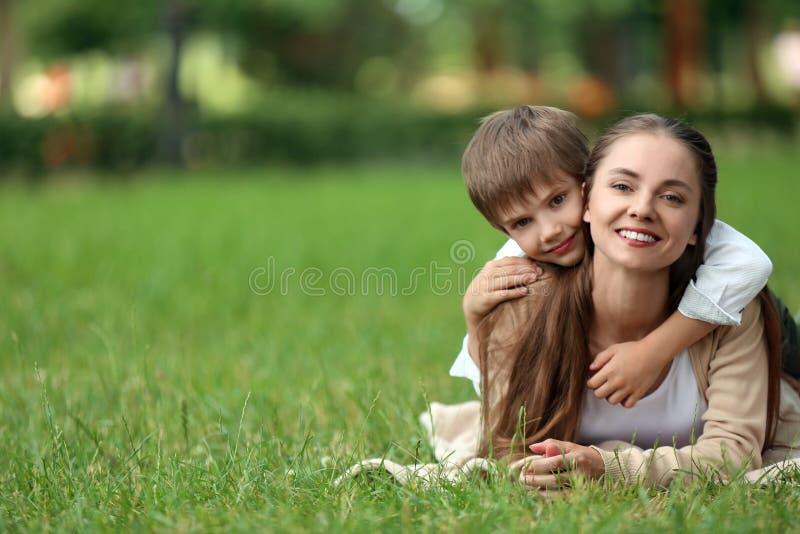 愉快的基于格子花呢披肩的母亲和儿子在绿色公园 免版税库存图片