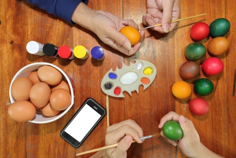愉快的基督徒家庭时间顶视图在期间鸡蛋为复活节天做准备 库存照片