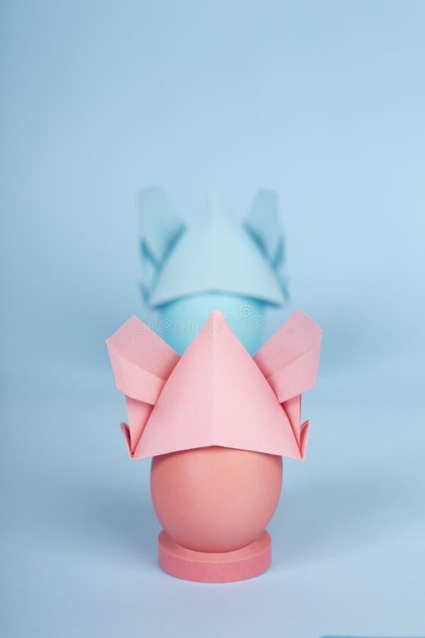 愉快的复活节假日概念洗染了鸡桃红色和蓝色鸡蛋在兔宝宝origami帽子 库存照片