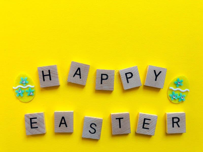 愉快的复活节 在黄色隔绝的词 创造性的概念 免版税库存图片