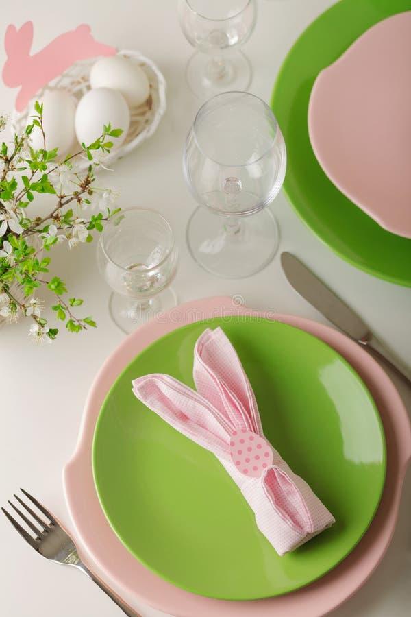 愉快的复活节 复活节桌的装饰和桌设置-开花的春天树分支,桃红色和绿色盘  免版税图库摄影