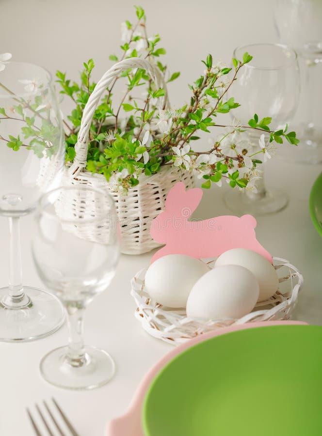 愉快的复活节 复活节桌的装饰和桌设置-开花的春天树分支,桃红色和绿色盘  库存照片