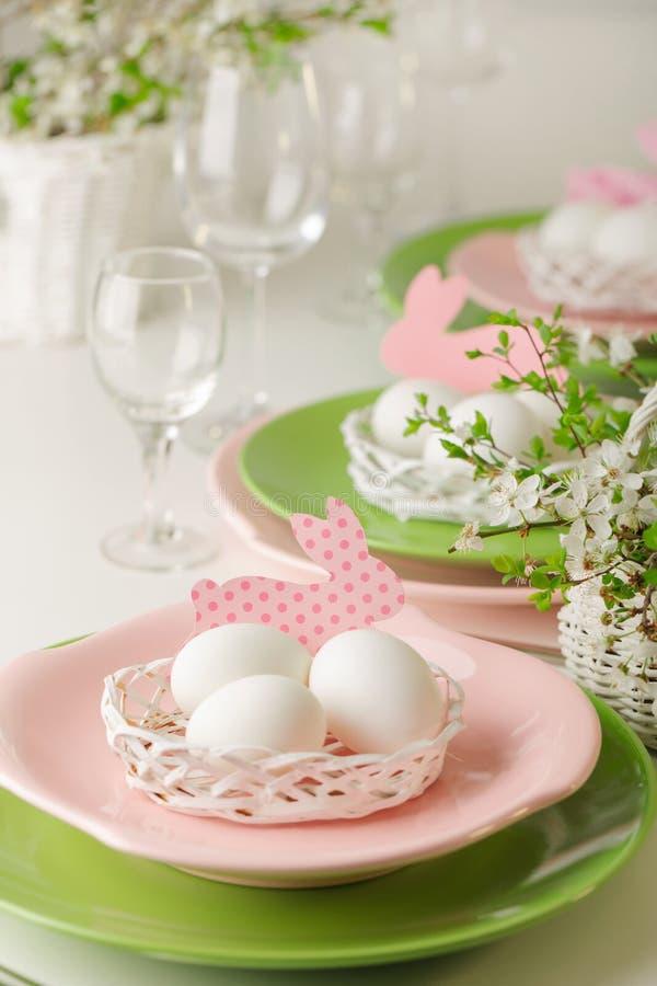 愉快的复活节 复活节桌的装饰和桌设置-开花的春天树分支,桃红色和绿色盘  免版税库存照片