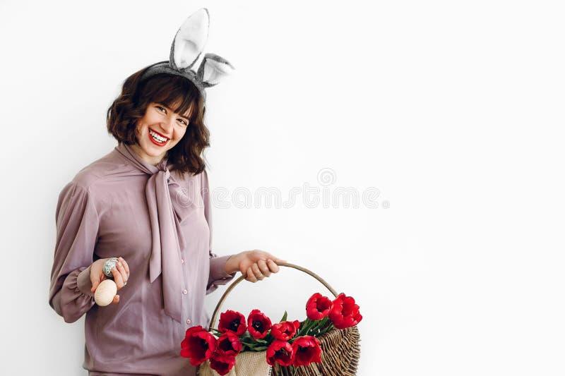 愉快的复活节 拿着baske的兔宝宝耳朵的美丽的时髦的女孩 库存图片