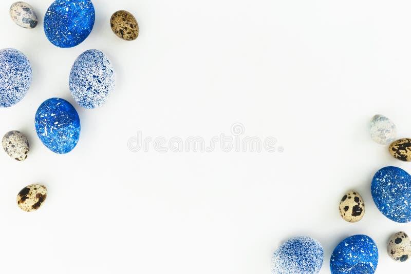 愉快的复活节 框架用蓝色有斑点的复活节彩蛋和鹌鹑蛋与在白色背景隔绝的拷贝空间 平的位置,顶视图 免版税库存照片