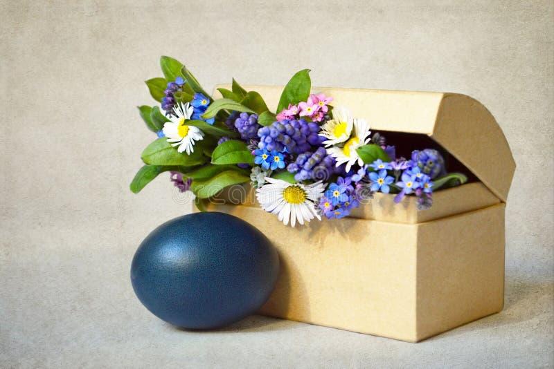 愉快的复活节卡片:在难看的东西背景的蓝色复活节彩蛋和春天花 库存图片