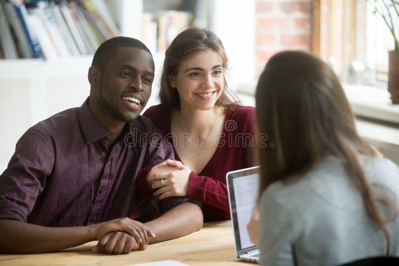 愉快的多种族夫妇被激发关于房子购买 免版税库存图片