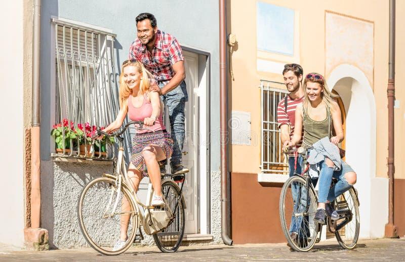 愉快的多种族朋友结合有乐趣骑马自行车 库存图片