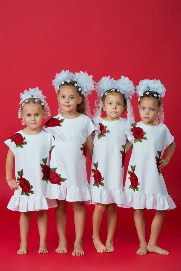 愉快的大四口之家被绣的白色礼服的姐妹在简单的红色背景在演播室 库存图片