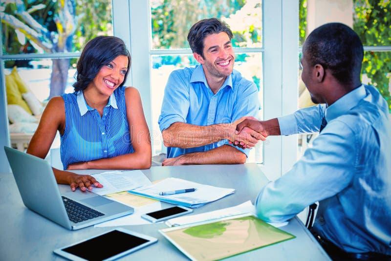 愉快的夫妇与不动产房地产经纪商握手 免版税库存照片