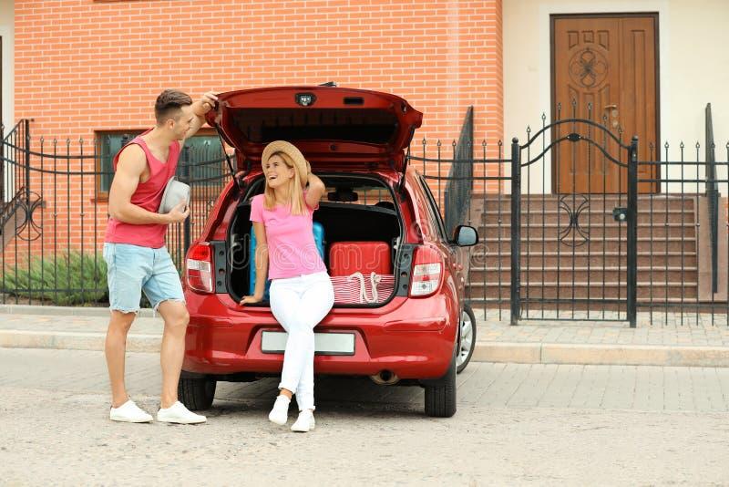 愉快的夫妇临近带着手提箱的车厢户外 免版税库存照片