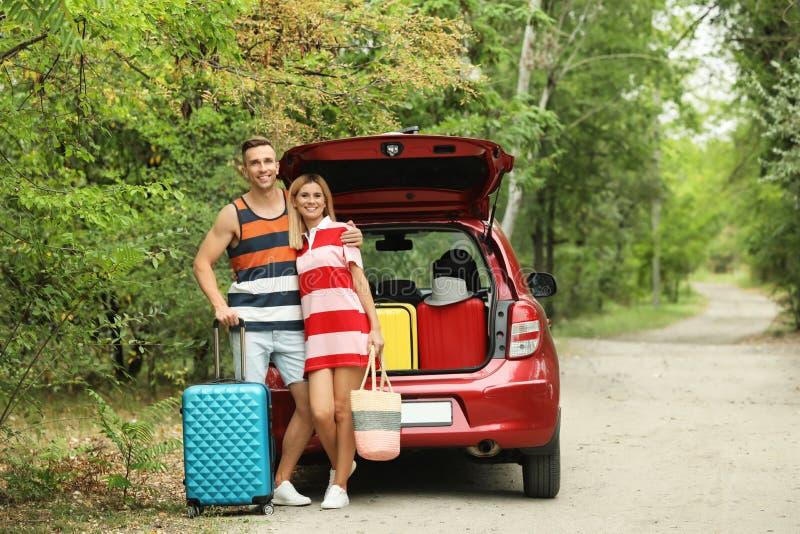 愉快的夫妇临近带着手提箱的车厢户外 免版税库存图片