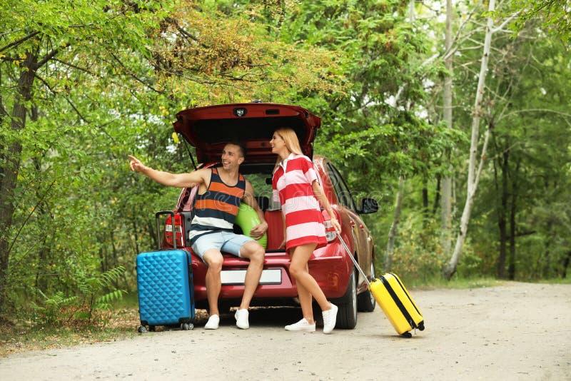 愉快的夫妇临近带着手提箱的车厢户外 免版税图库摄影