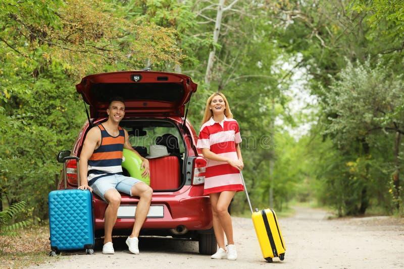 愉快的夫妇临近带着手提箱的车厢户外 库存照片