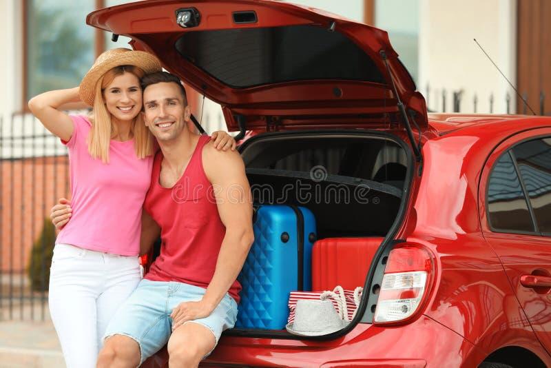 愉快的夫妇临近带着手提箱的车厢 免版税库存图片