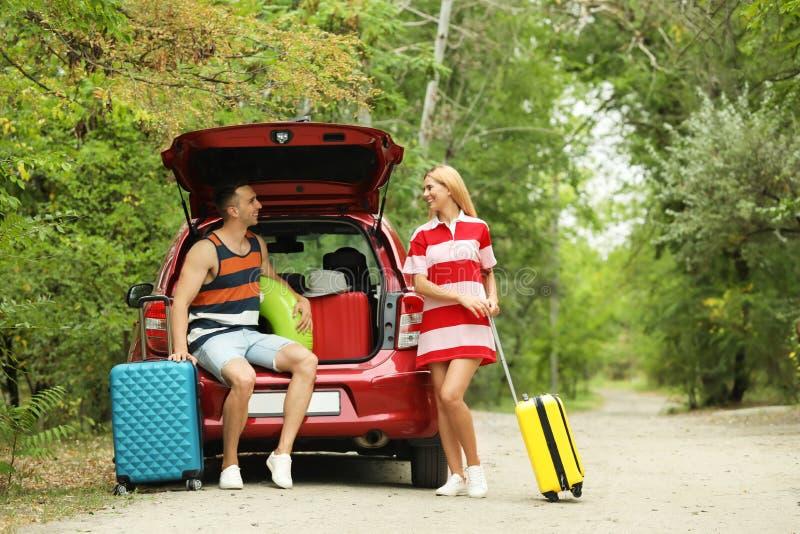 愉快的夫妇临近带着手提箱的车厢 库存图片