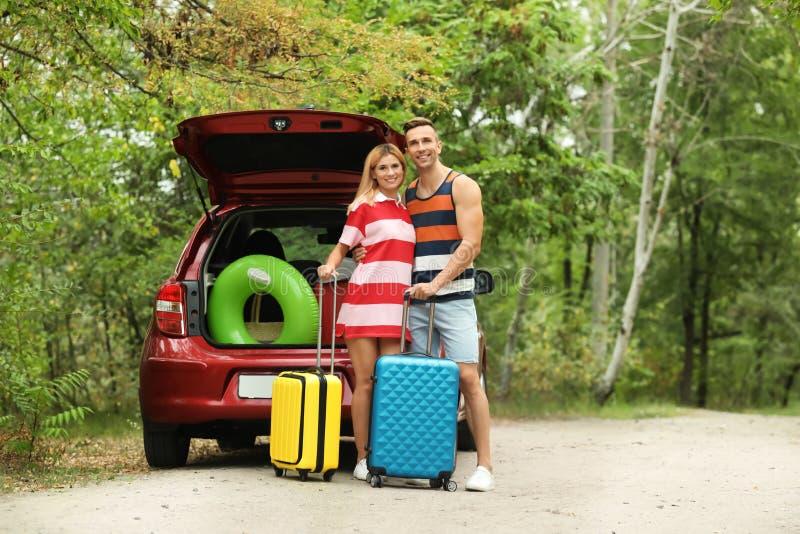 愉快的夫妇临近带着手提箱的车厢 图库摄影