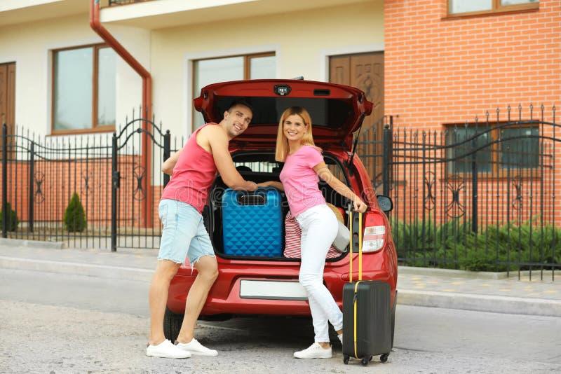 愉快的夫妇临近带着手提箱的车厢 库存照片