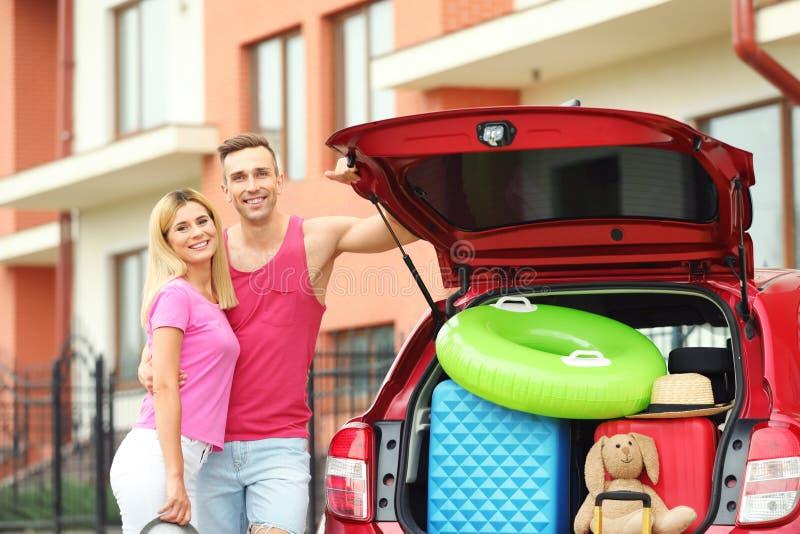 愉快的夫妇临近带着手提箱的车厢 免版税库存照片