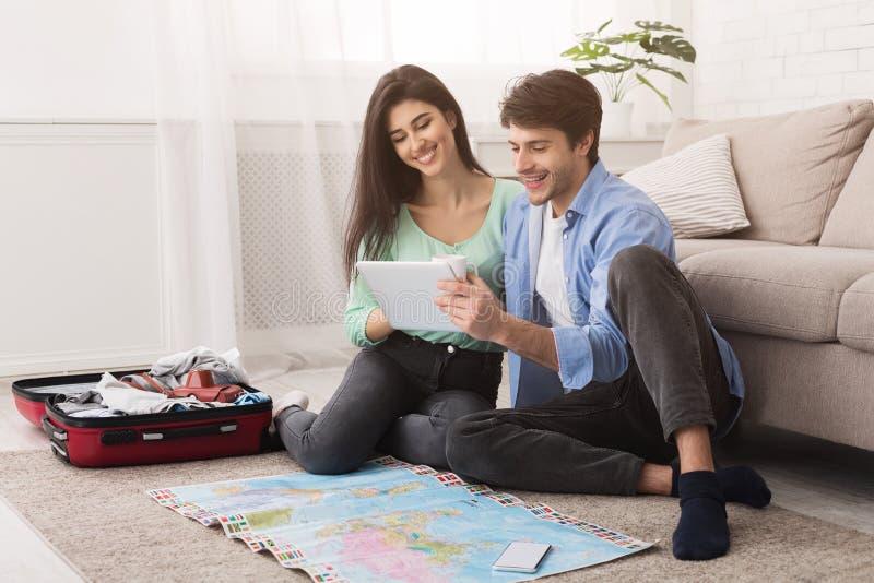 愉快的夫妇为假期做准备,使用片剂 免版税库存图片
