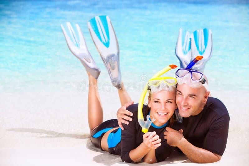 愉快的夫妇享受海滩活动 免版税库存照片
