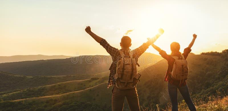 愉快的夫妇人和妇女游人在山顶部在日落 免版税库存图片