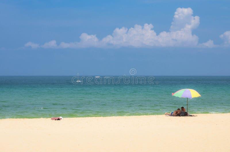 愉快的夫妇人在五颜六色的伞下基于美丽的热带海滩在普吉岛 库存图片