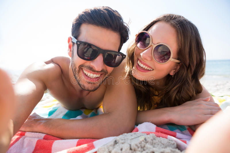 愉快的夫妇佩带的太阳镜画象,当一起说谎在毯子在海滩时 免版税库存图片