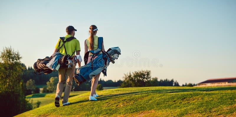 愉快的夫妇佩带的高尔夫球成套装备,当运载的立场请求时 免版税库存图片