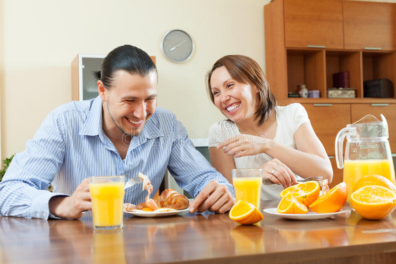 愉快的夫妇吃早餐用汁液在早晨在家 免版税库存照片