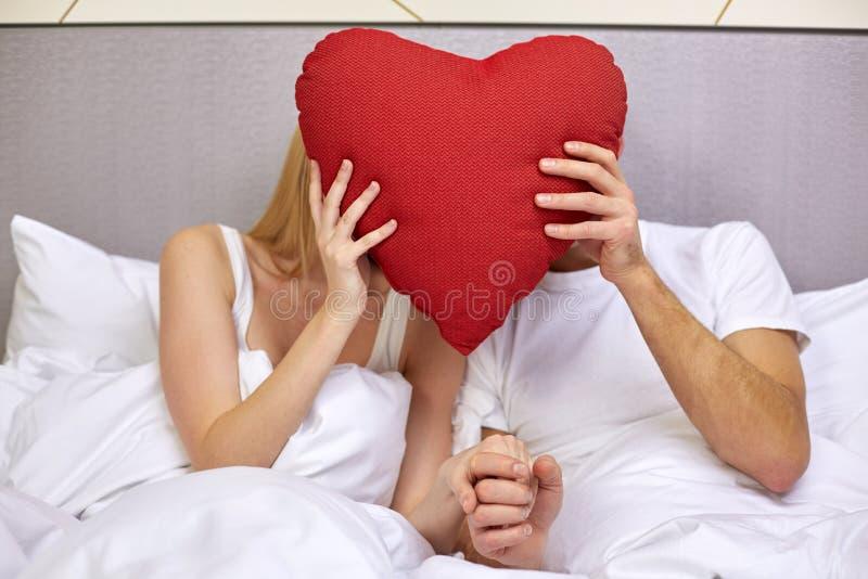 愉快的夫妇在与红色心脏形状的床上把枕在 免版税库存照片