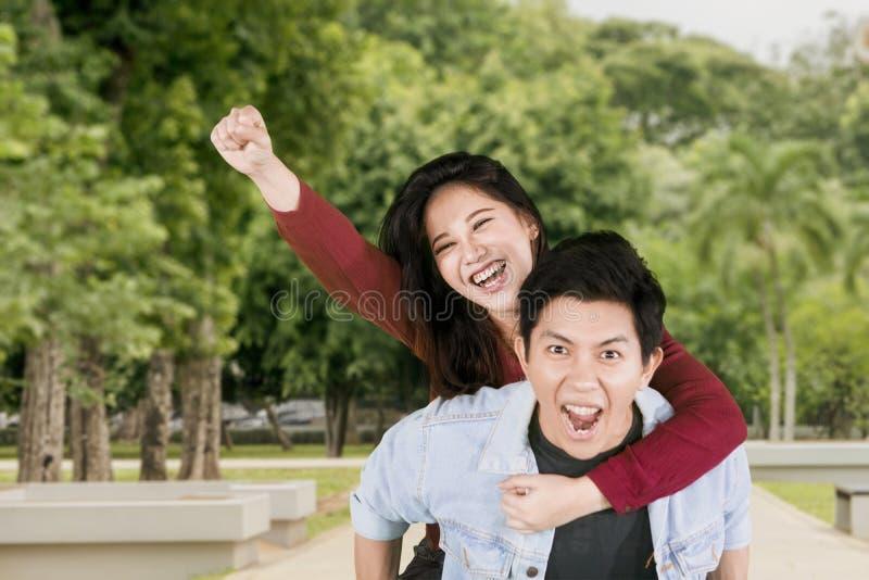 愉快的夫妇在公园播放肩扛乘驾 免版税库存图片