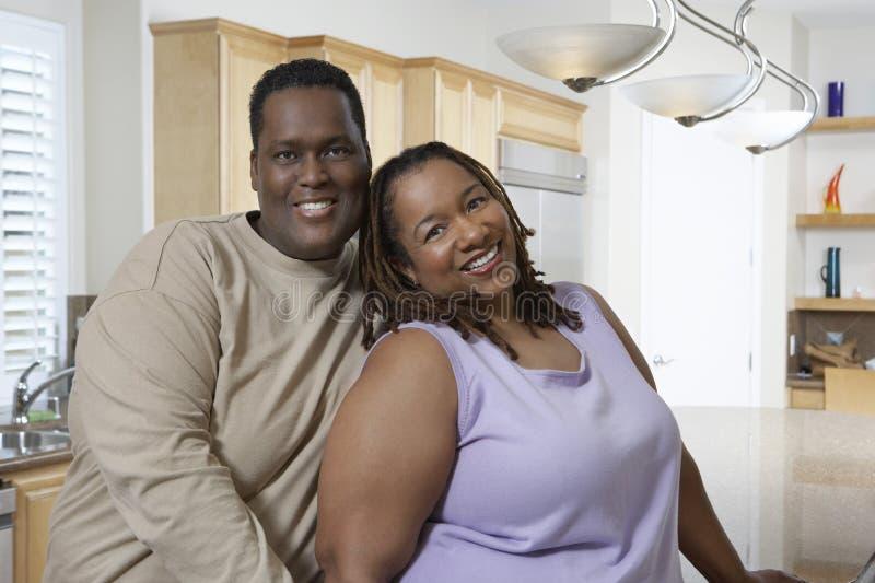 愉快的夫妇在厨房里 免版税库存照片