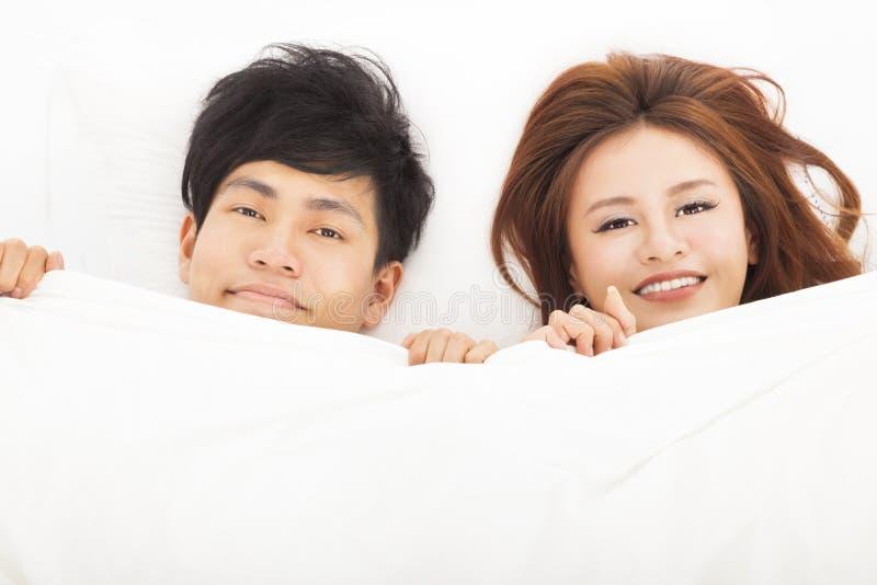 愉快的夫妇在床上 免版税库存图片