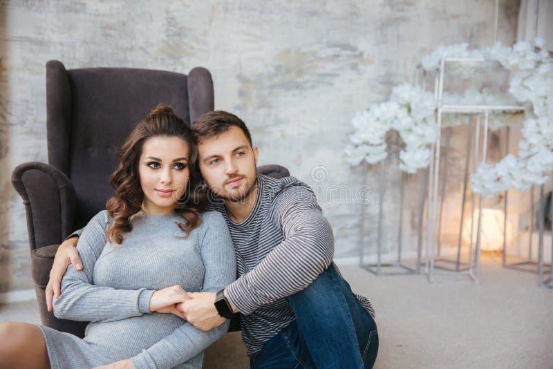 愉快的夫妇在椅子附近坐在他们的房子里 有她心爱的丈夫的孕妇 新年度 免版税图库摄影