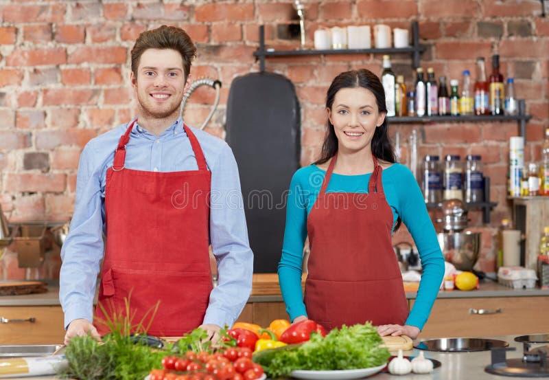 愉快的夫妇在烹饪课的厨房里 免版税图库摄影
