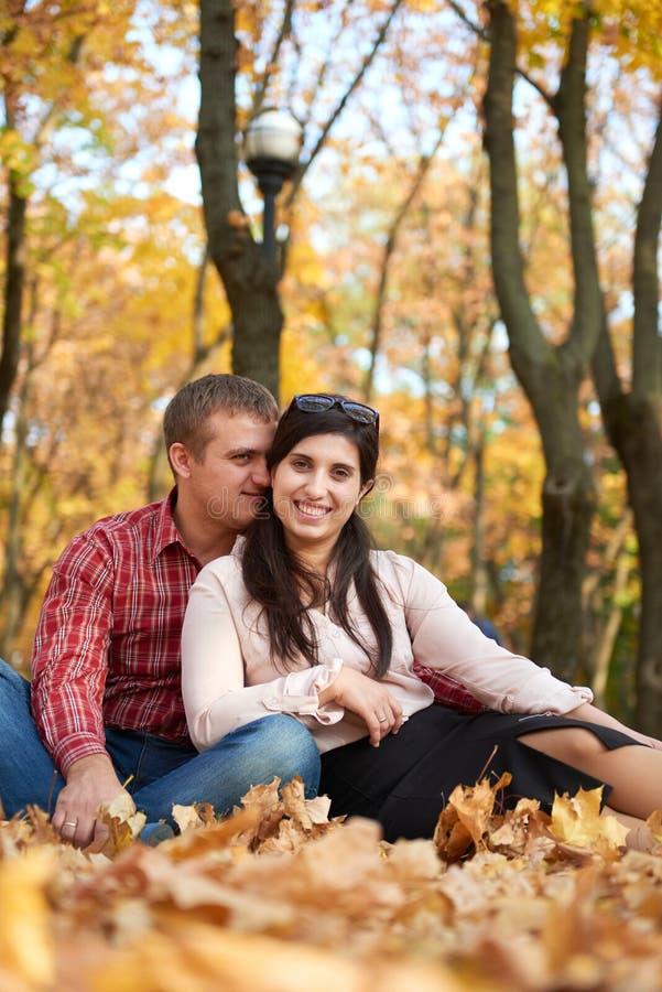 愉快的夫妇在秋天城市公园坐 明亮的黄色树 免版税库存照片