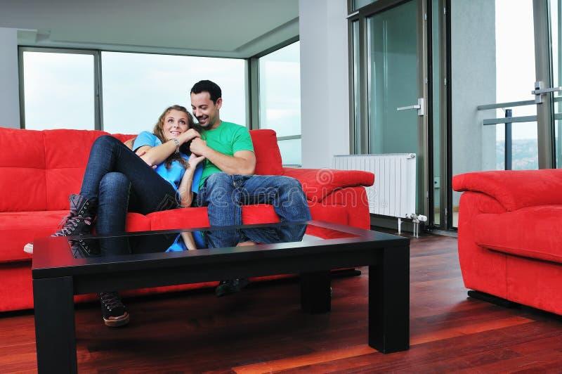 愉快的夫妇在红色沙发放松 免版税库存图片