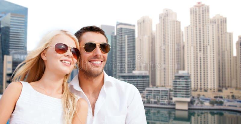 愉快的夫妇在迪拜市背景的树荫下 免版税图库摄影