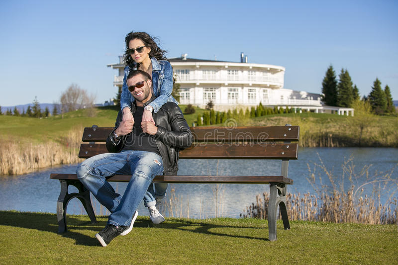 年轻愉快的夫妇在长凳拥抱在公园 库存图片