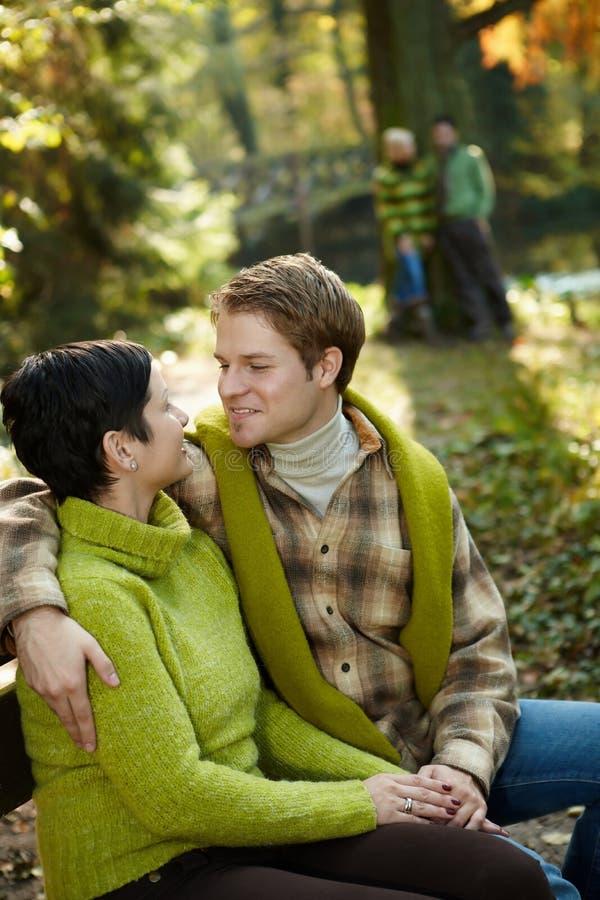 愉快的夫妇坐公园长椅 图库摄影