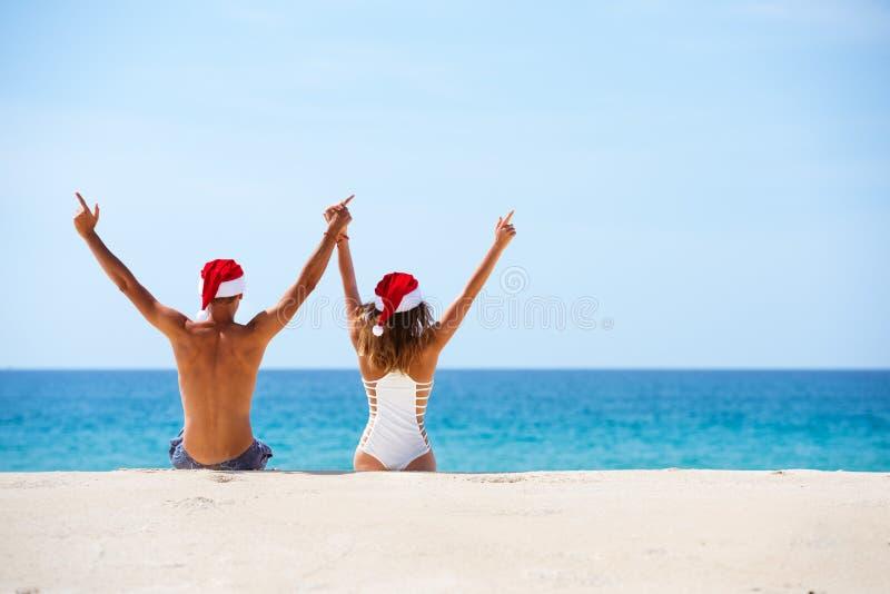 愉快的夫妇坐在圣诞节帽子的白色海滩 图库摄影
