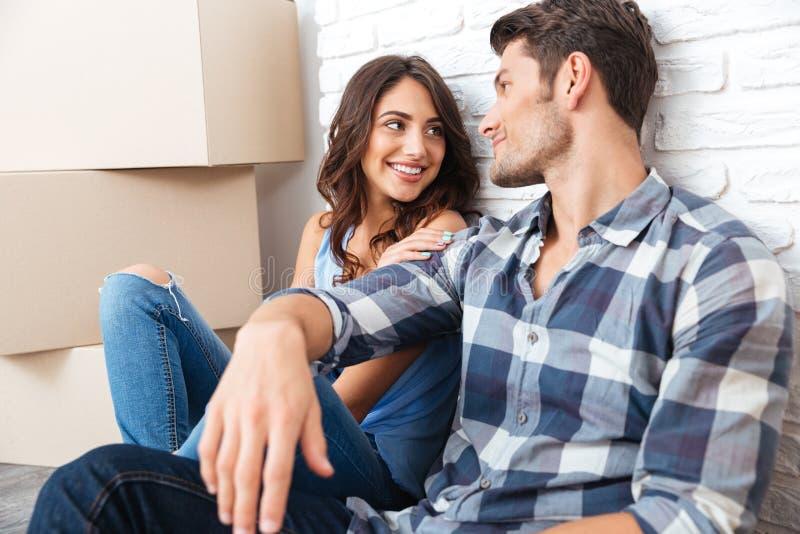 愉快的夫妇坐地板在箱子附近在买房子以后 免版税库存照片