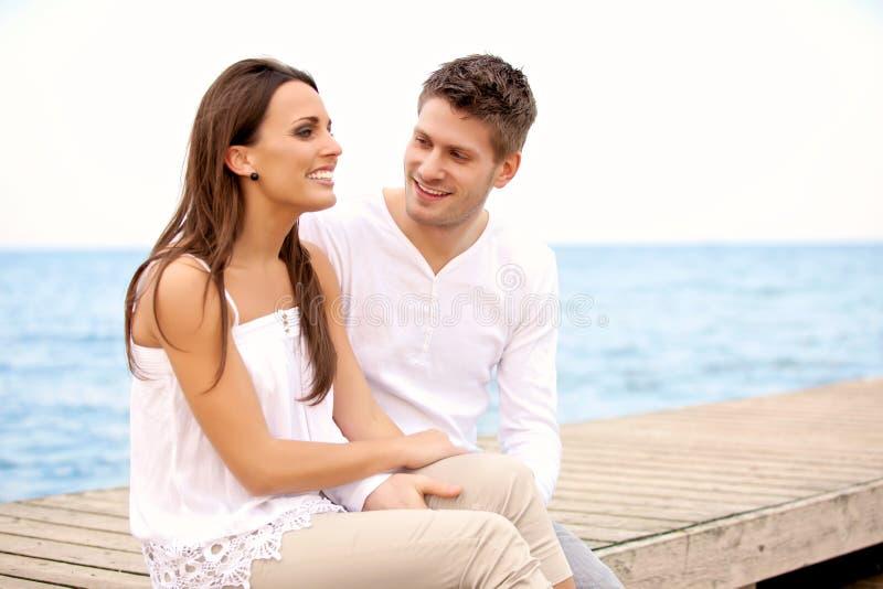 愉快的夫妇坐码头 免版税库存照片