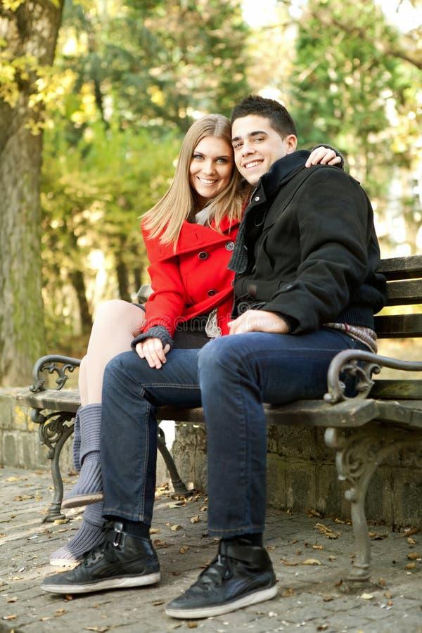 愉快的夫妇坐长凳 免版税库存图片
