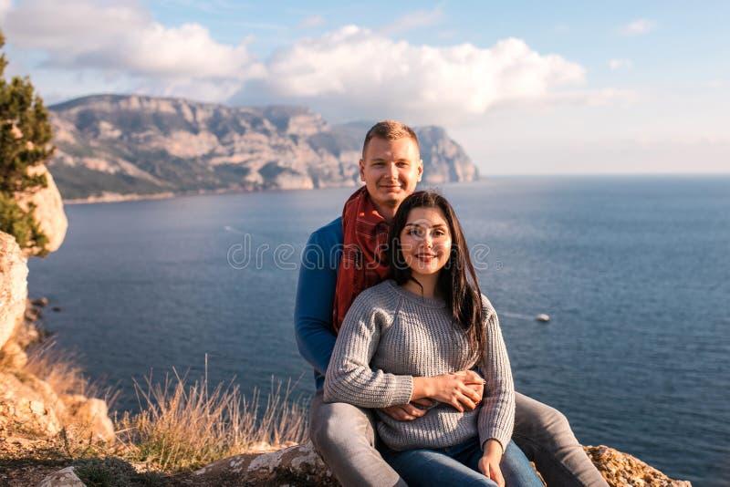 愉快的夫妇就座室外在黑海附近 库存图片