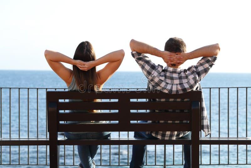 愉快的夫妇放松的坐在海滩的一条长凳 库存照片