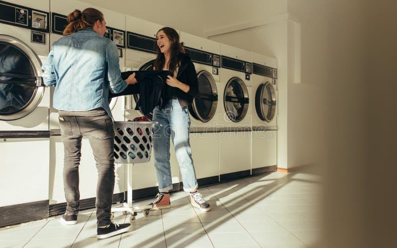愉快的夫妇洗涤的衣裳一起在洗衣房 免版税库存照片