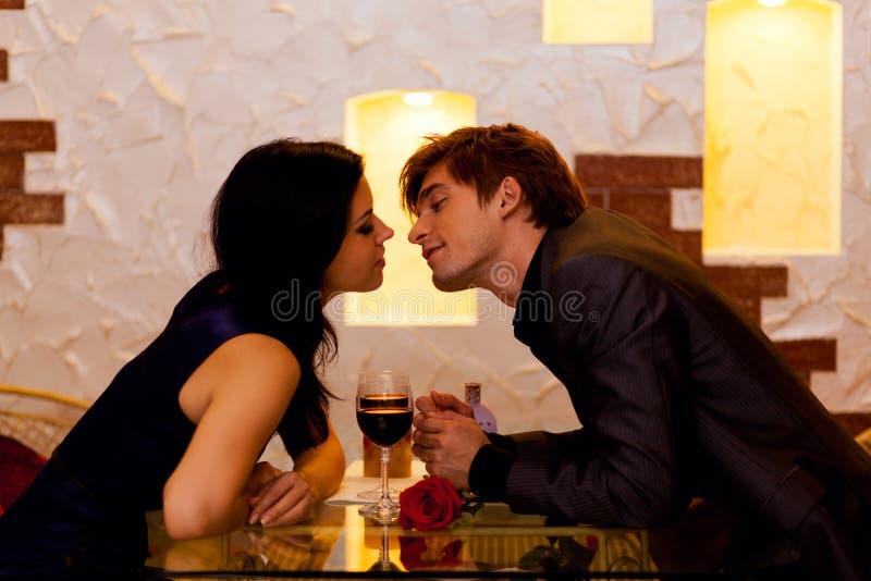 年轻愉快的夫妇浪漫亲吻的日期与 免版税库存照片