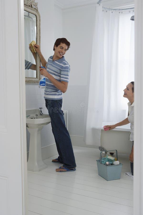 愉快的夫妇清洁卫生间 免版税库存照片